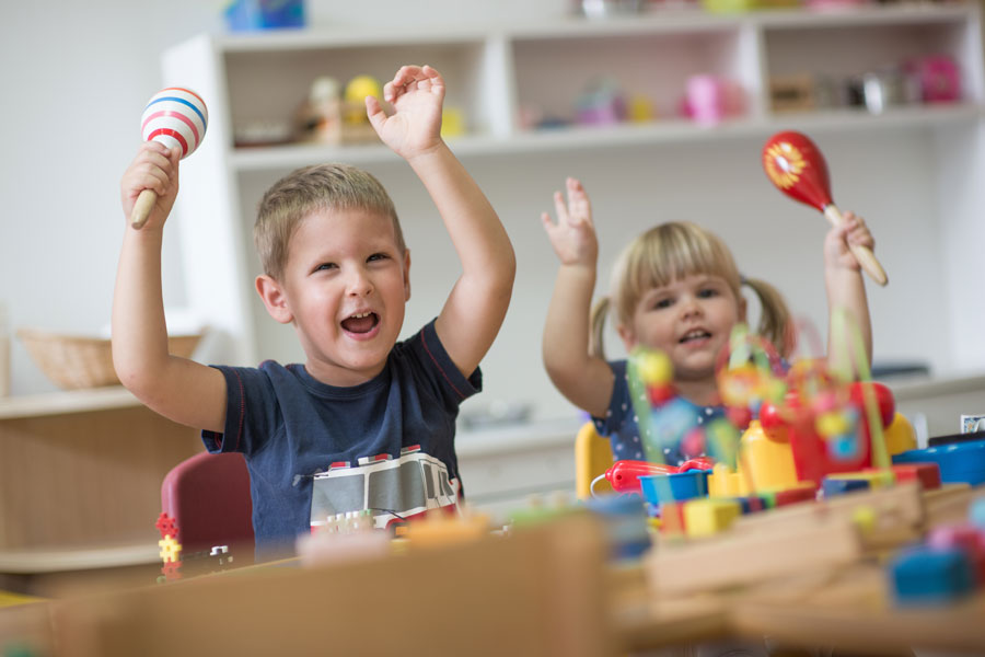 Two children playing with toys at a desk